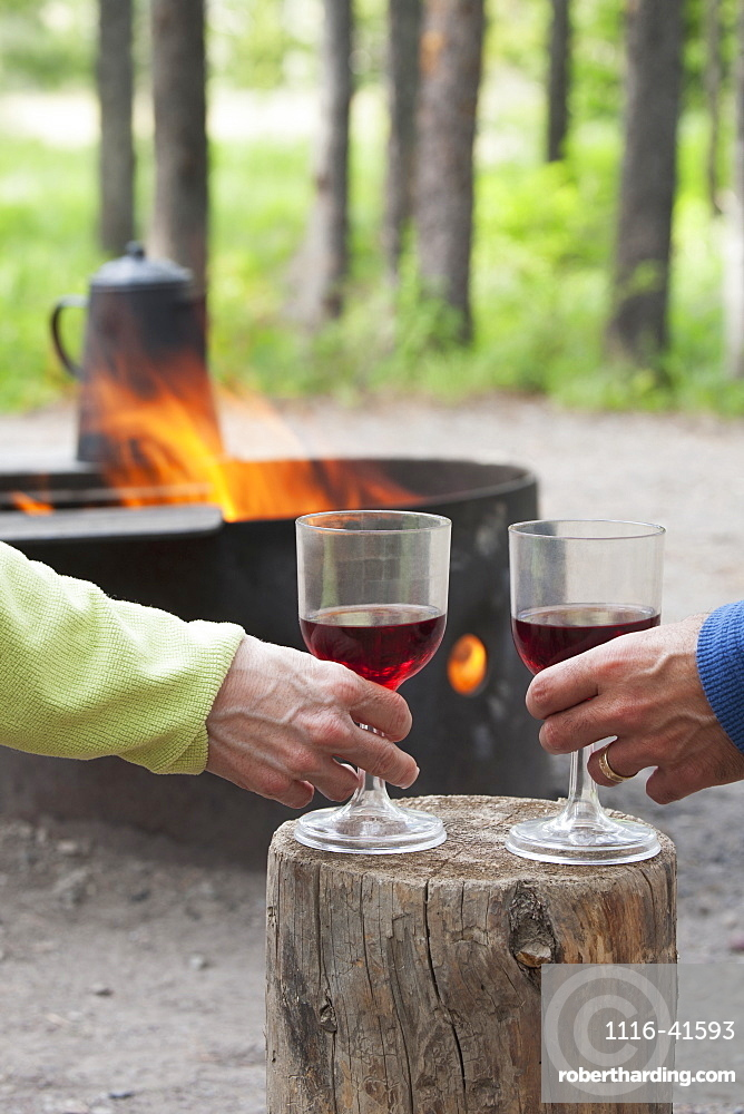 A Couple Holding Wine Glasses On A Block Of Wood With A Fire Pit Burning In A Campground, Waterton, Alberta, Canada
