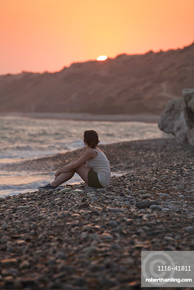 A woman sits on the rock beach looking out to the ocean at sunset, Aphrodite bay, cyprus