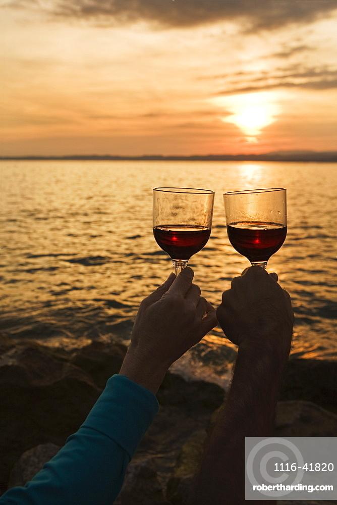 A couple holding wine glasses up at sunset over a lake, Bardolino veneto italy