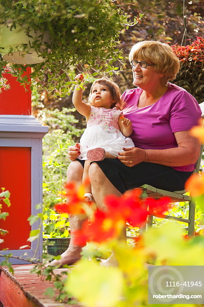 Grandmother And Child Sitting On Front Porch With Many Plants Surrounding Them, Winnipeg Manitoba Canada