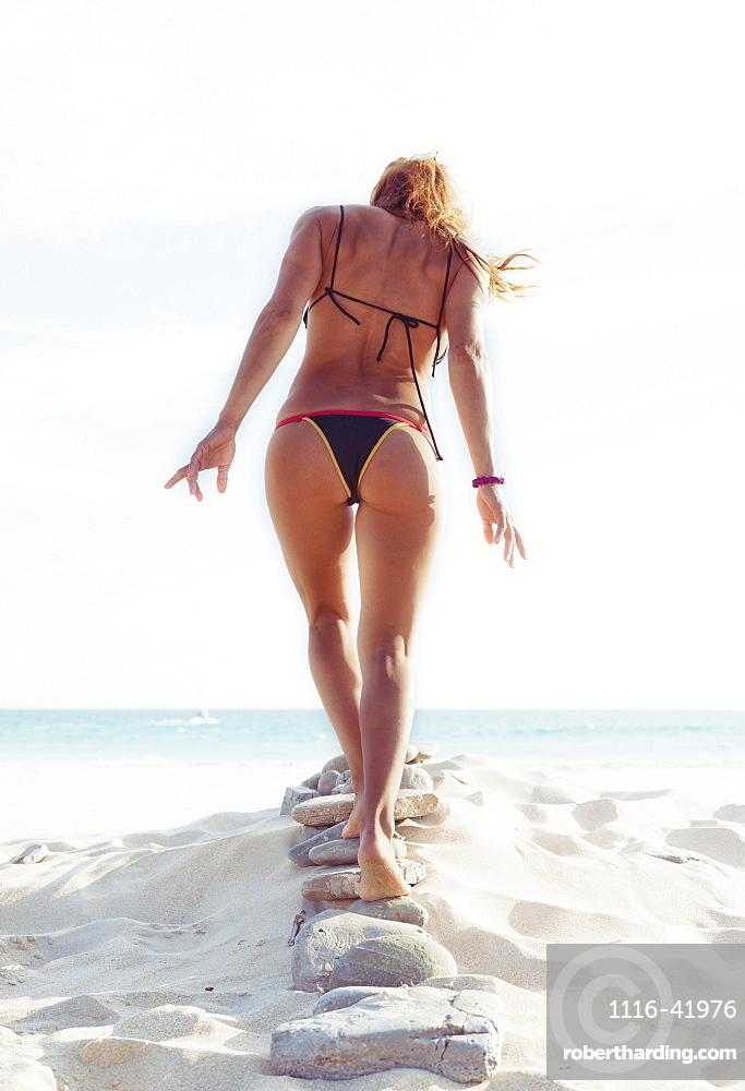 A woman in a bikini walks on a row of rocks in the sand on a beach, Tarifa cadiz andalusia spain