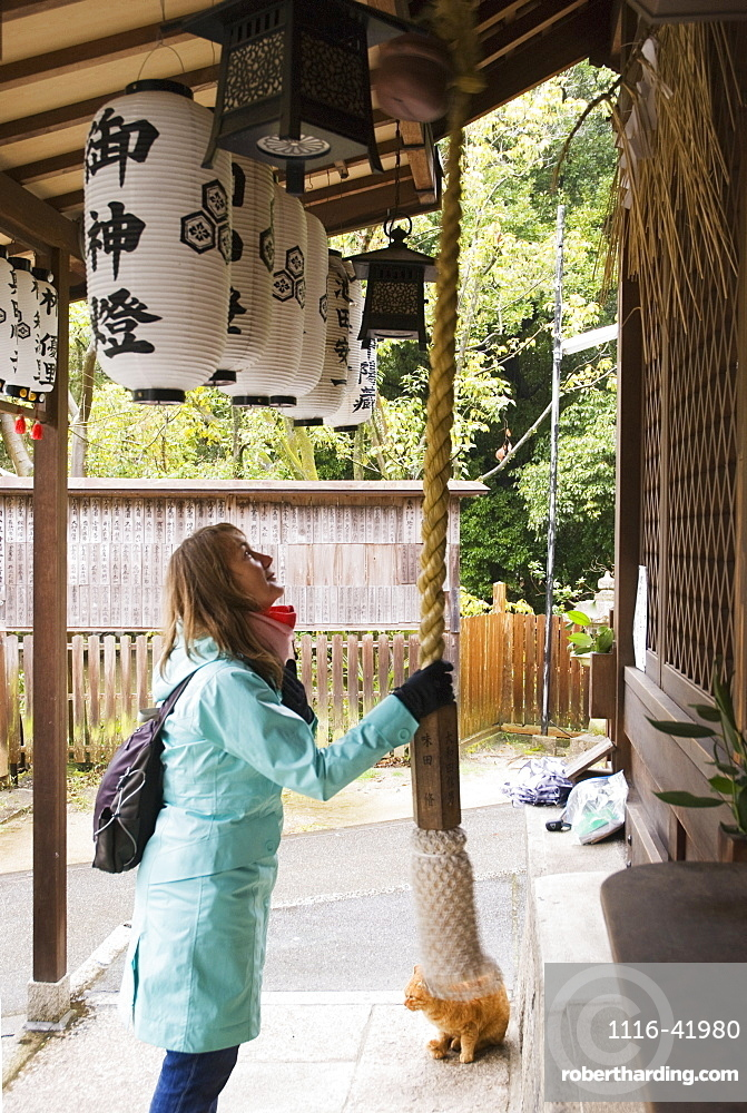 Female tourist ringing the bell of a japanese shrine, Kyoto japan