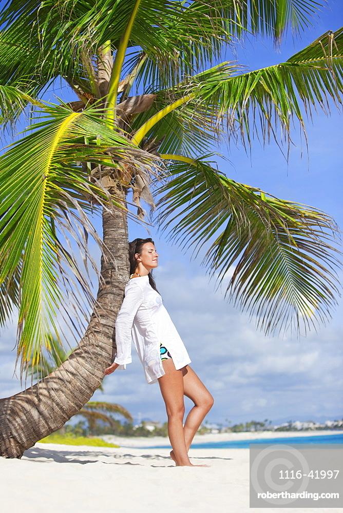 A Woman In A White Dress Posing Beside A Palm Tree On A Beach, Punta Cana, La Altagracia, Dominican Republic
