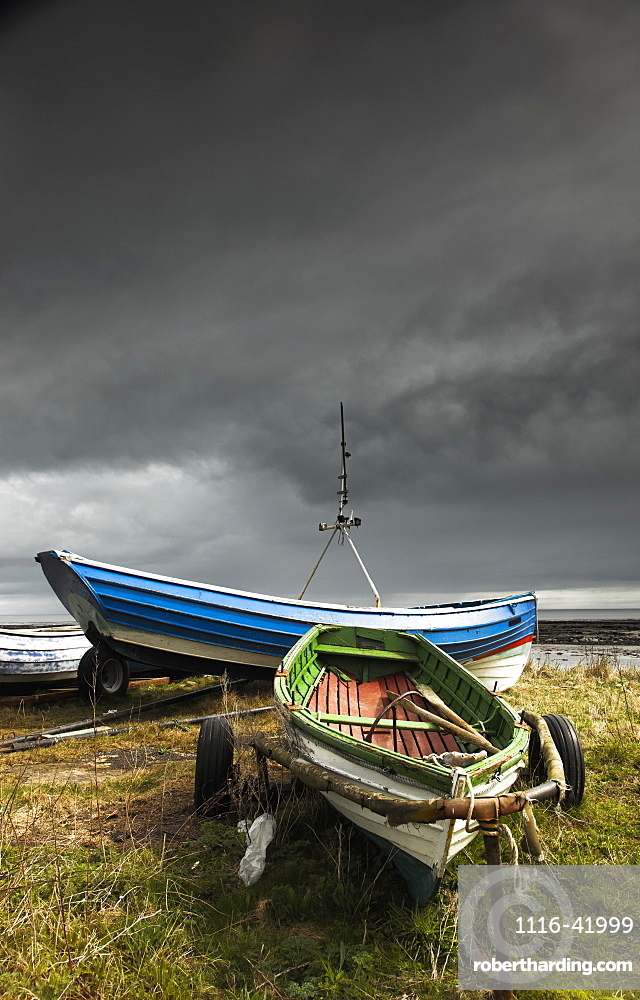 Rowboats sitting on trailers on the shore under storm clouds, Boulmer northumberland england