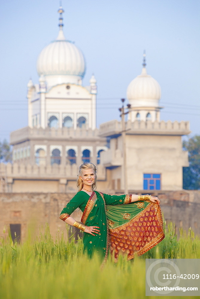 Portrait Of A Blond Woman Wearing A Sari In A Field With A Temple In The Background, Ludhiana, Punjab, India