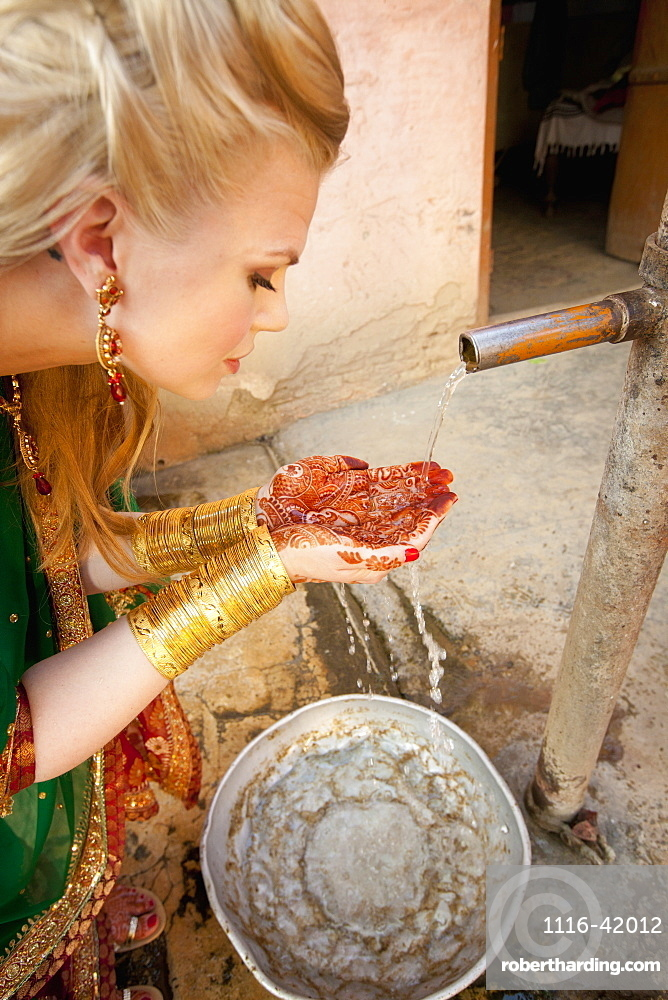 A Woman With Mehndi On Her Palms Cups Her Hands To Collect Water From A Tap, Ludhiana, Punjab, India