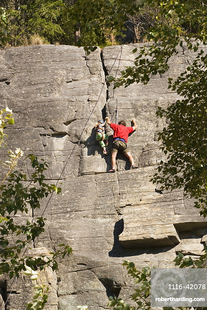 Mid-Age Man Climbing With Daughter (Age 5) Up Granite Cliff At Stone Hills Near Rexford, Montana, Usa