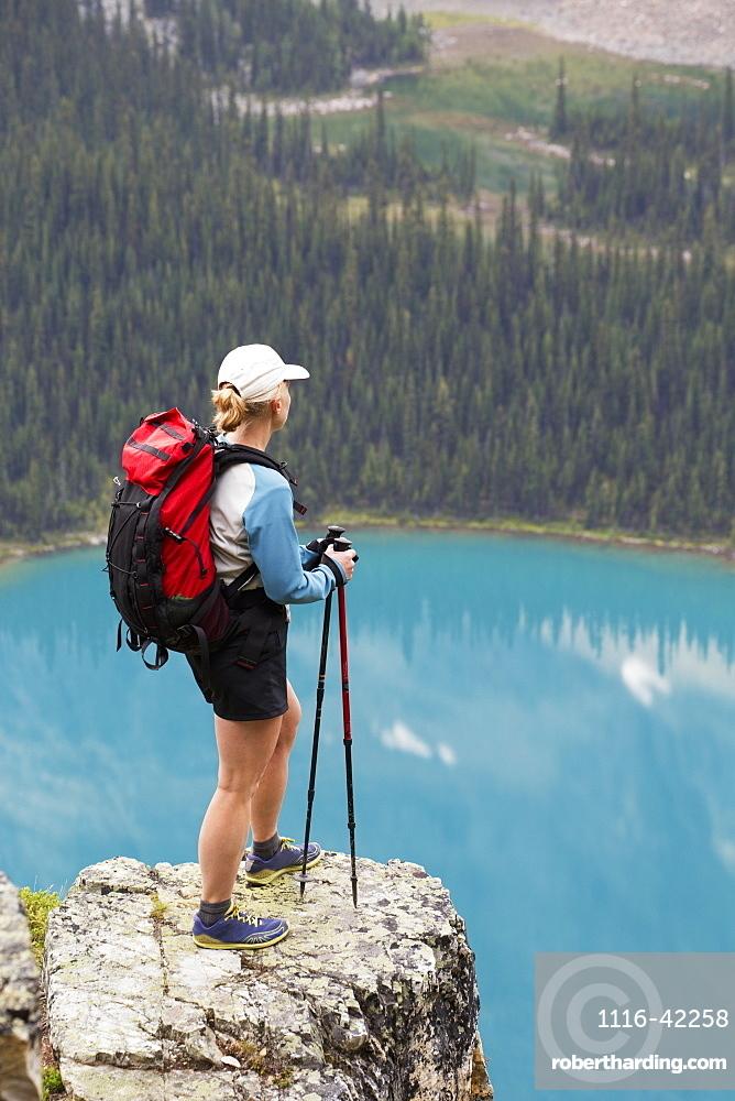 Female Hiker On Rock Cliff Overlooking Blue Alpine Lake, British Columbia, Canada