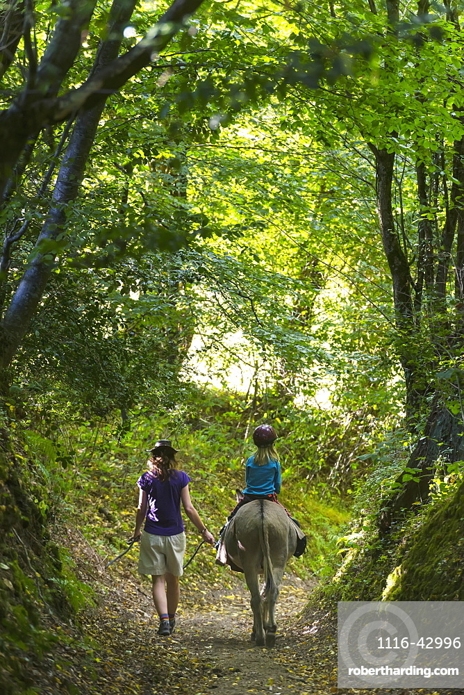 Mother With Girl On Donkey Walking Along A Trail, Normandy, France