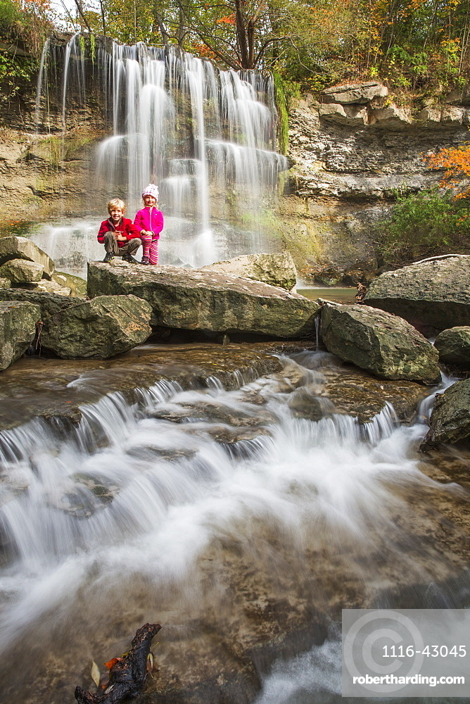 Brother And Sister Pose In Front Of A Waterfall In Rock Glen Conservation Area, Ontario, Canada