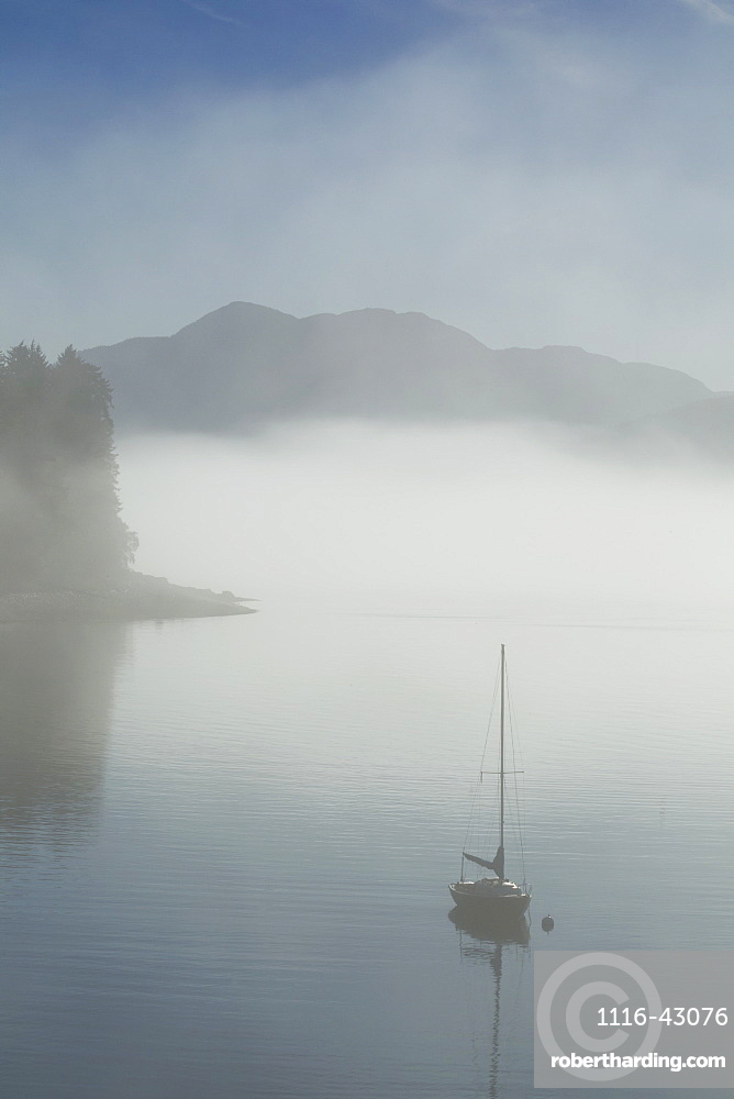 Low Fog And Mist Burn Off Along The Shoreline In Alaska's Inside Passage Where A Sailboat Rests At Anchor In A Small Cove Near Juneau, Alaska. Tongass National Forest.