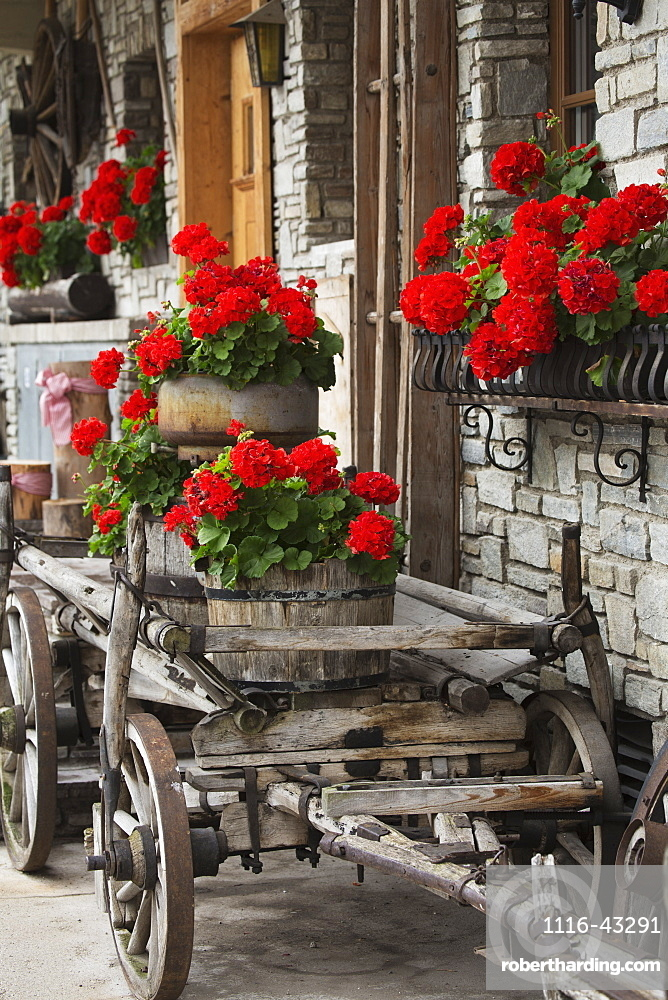 A Wooden Cart With Barrels Full Of Red Flowers Next To A Stone Building With Full Flower Boxes, Lanserbach, Austria