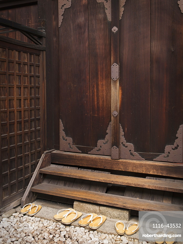 Japanese Shrine With Wooden Door And Slippers On Rock Steps, Kyoto, Japan