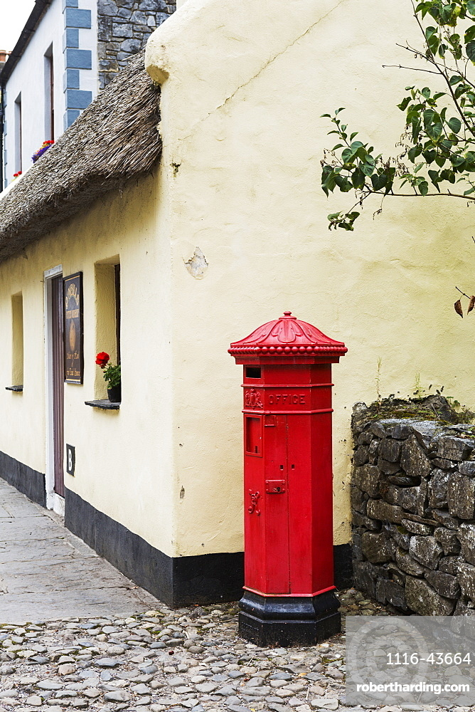 Red Mailbox Standing On Cobblestone Next To Stone Fence With Thatched Roof Building In Background, Bunratty, County Clare, Ireland