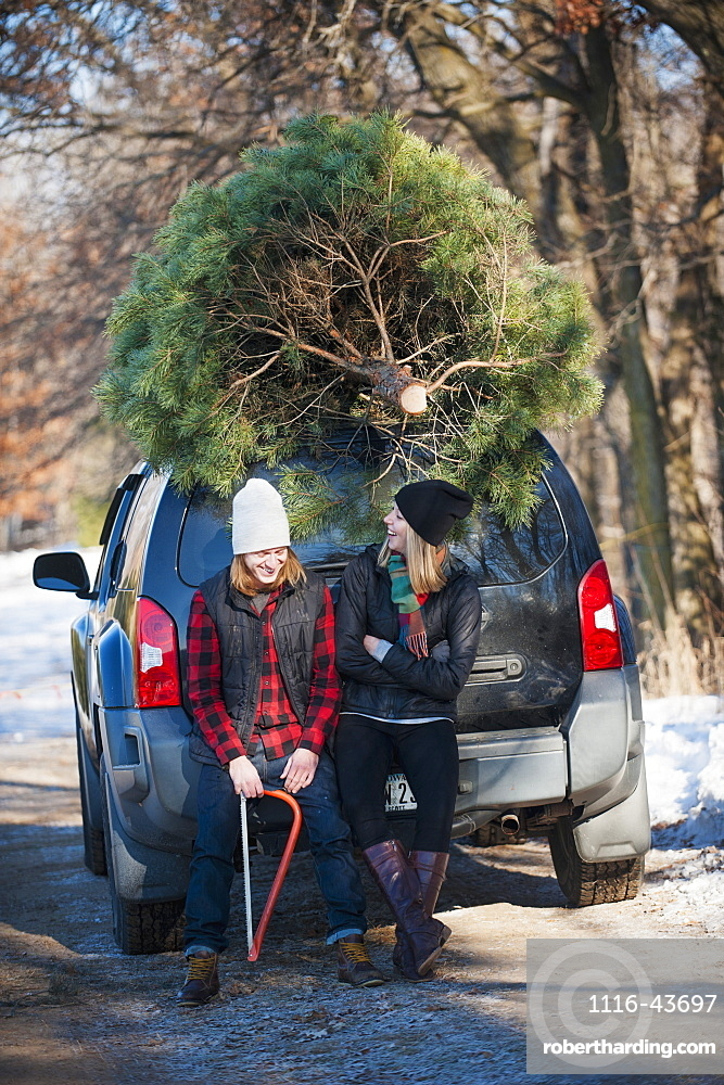 A Couple Sits On Their Vehicle With Their Fresh Cut Christmas Tree At A Christmas Tree Farm, Minnesota, United States Of America