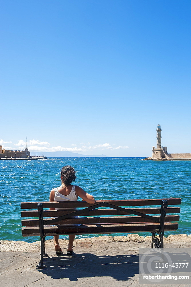 A Woman Sits On A Bench Overlooking The Harbour And Lighthouse, Chania, Crete, Greece