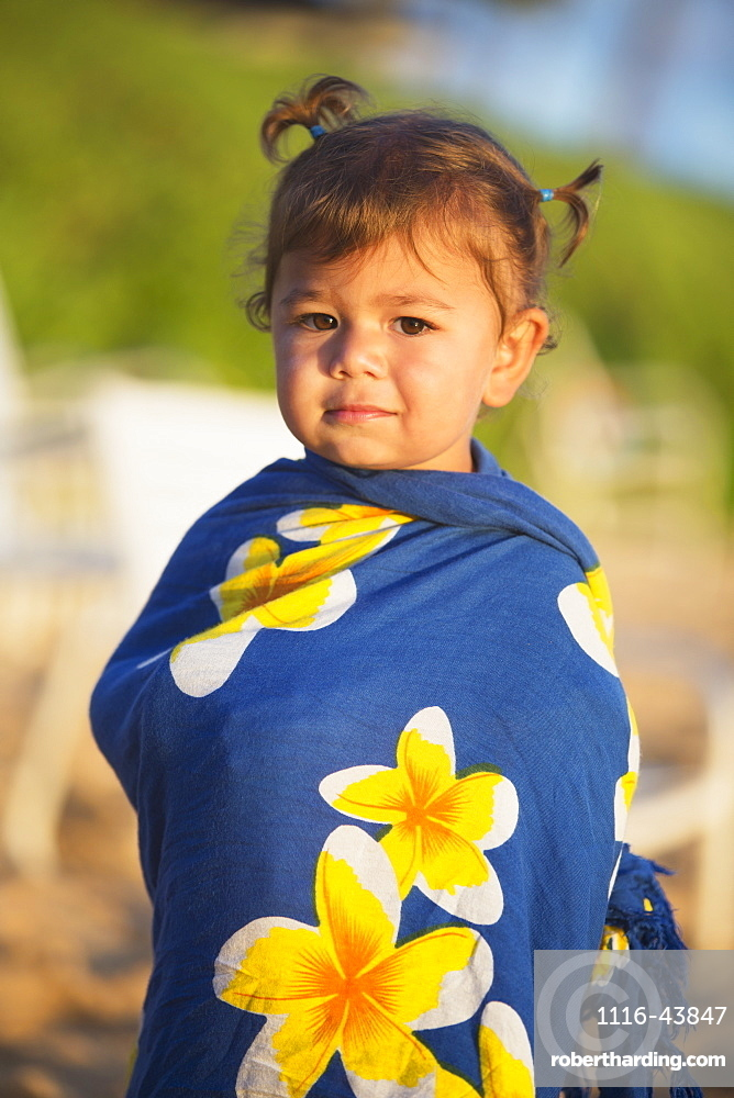 Portrait Of A Toddler Girl Wrapped In A Tropical Sarong On The Beach, Poipu, Kauai, Hawaii, United States Of America