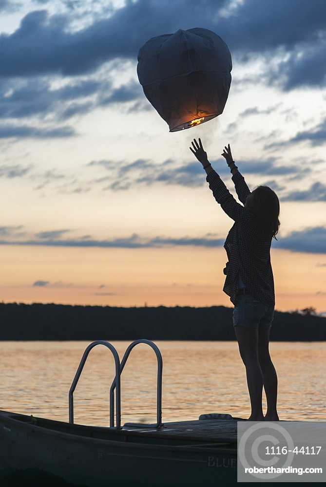 Silhouette Of A Girl Releasing A Lit Paper Lantern Into The Air At Sunset, Lake Of The Woods, Ontario, Canada