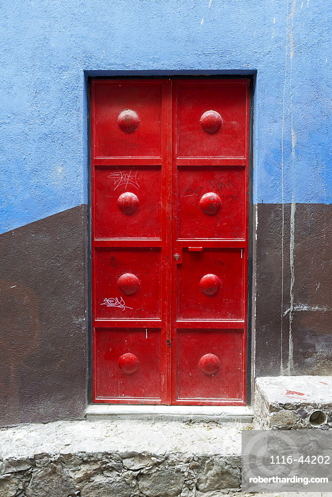 Red Metal Door On A Wall Painted Brown And Blue, San Miguel De Allende, Guanajuato, Mexico