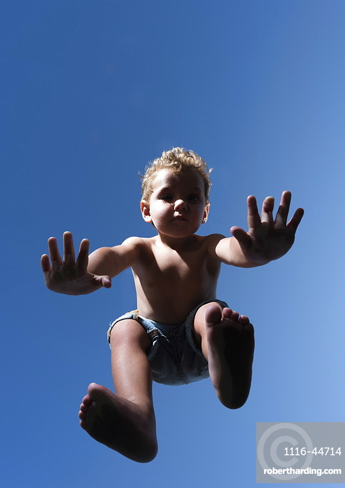 Low Angle View Of A Child In Mid-Air Against A Blue Sky, Tarifa, Cadiz, Andalusia, Spain