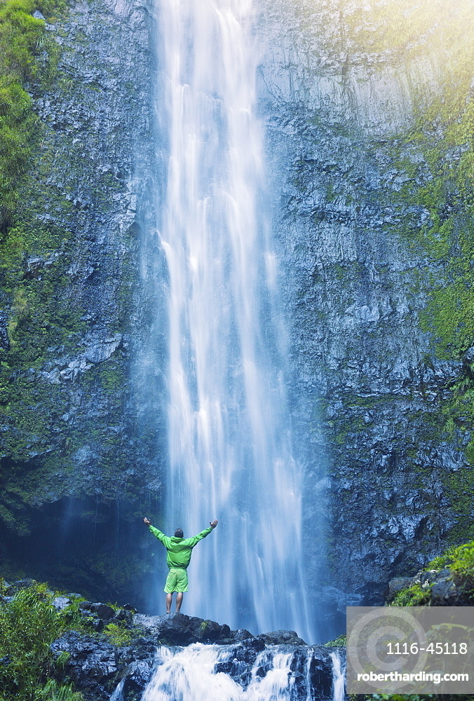 Man Standing At The Base Of Large Waterfall In Hawaii