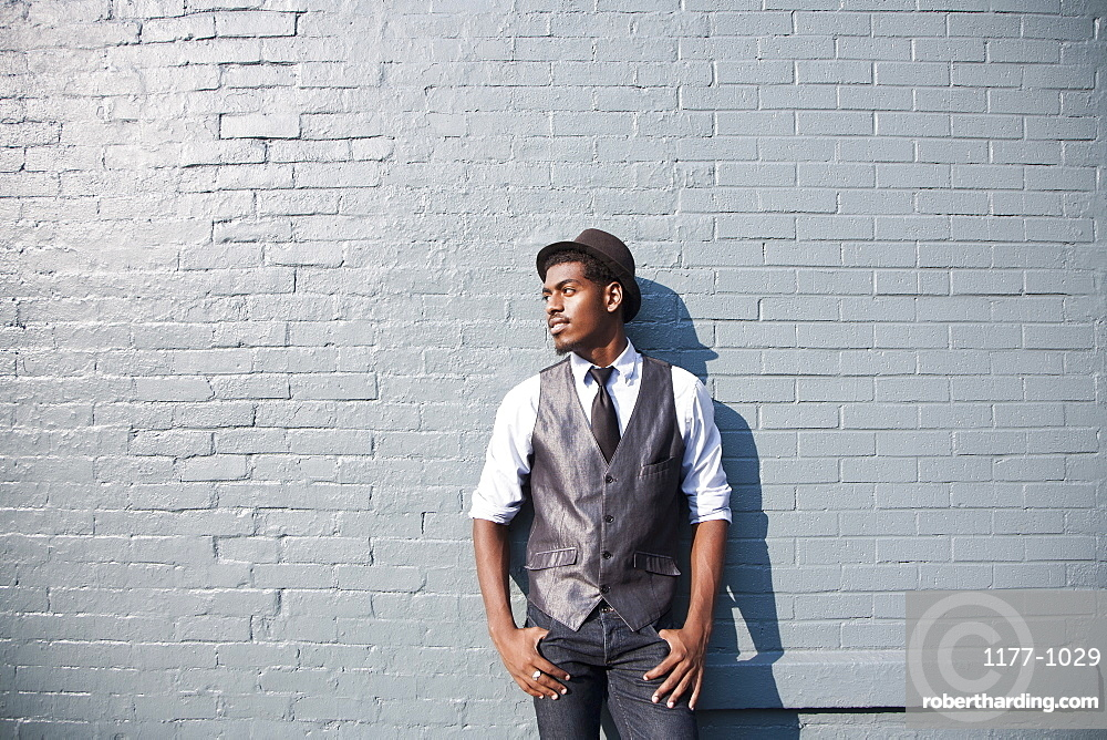A young black man leaning against a brick wall