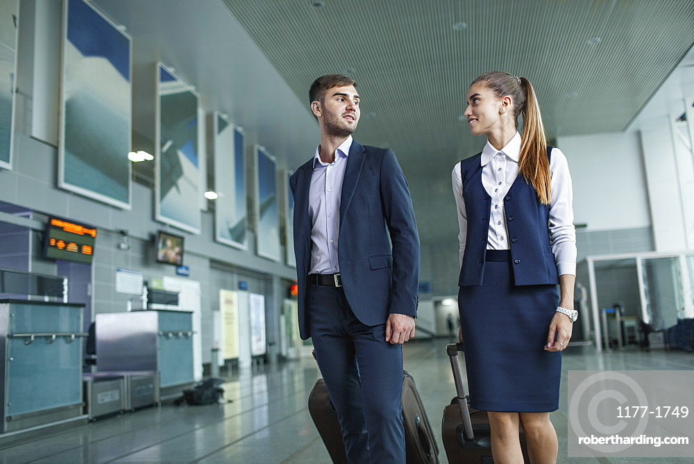 Young business people looking at each other while walking in airport