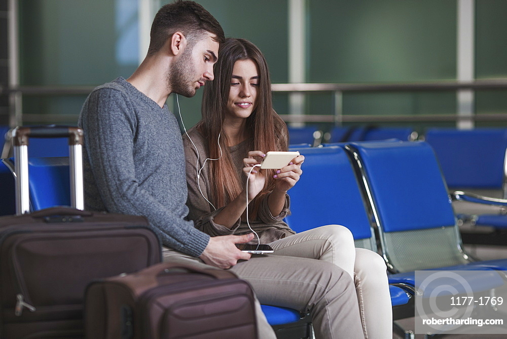 Young couple listening music through smart phone while waiting in airport