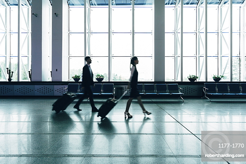 Full length side view of business people with luggage walking at airport