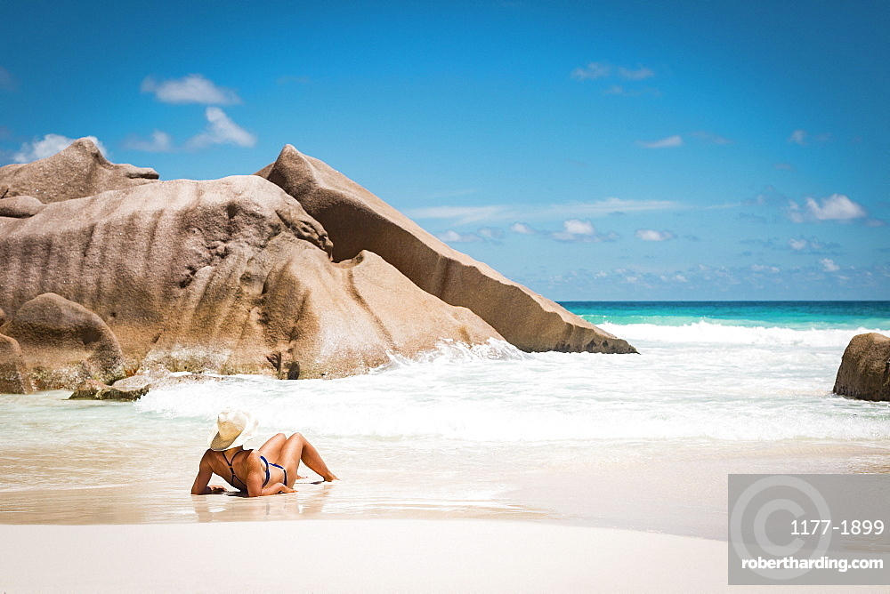 Rear view of mid adult woman in bikini relaxing at beach against blue sky, Seychelles