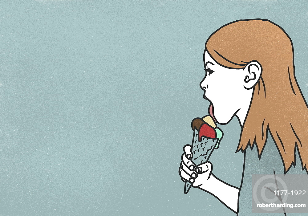 Woman licking ice cream cone on blue background