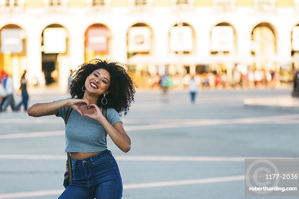 Portrait enthusiastic young woman forming heart-shape with hands in Praca do Comercio, Lisbon