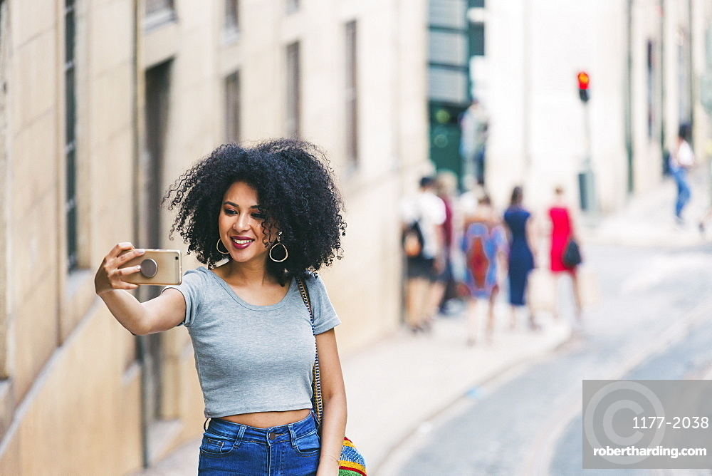 Young woman with smart phone taking selfie on urban street