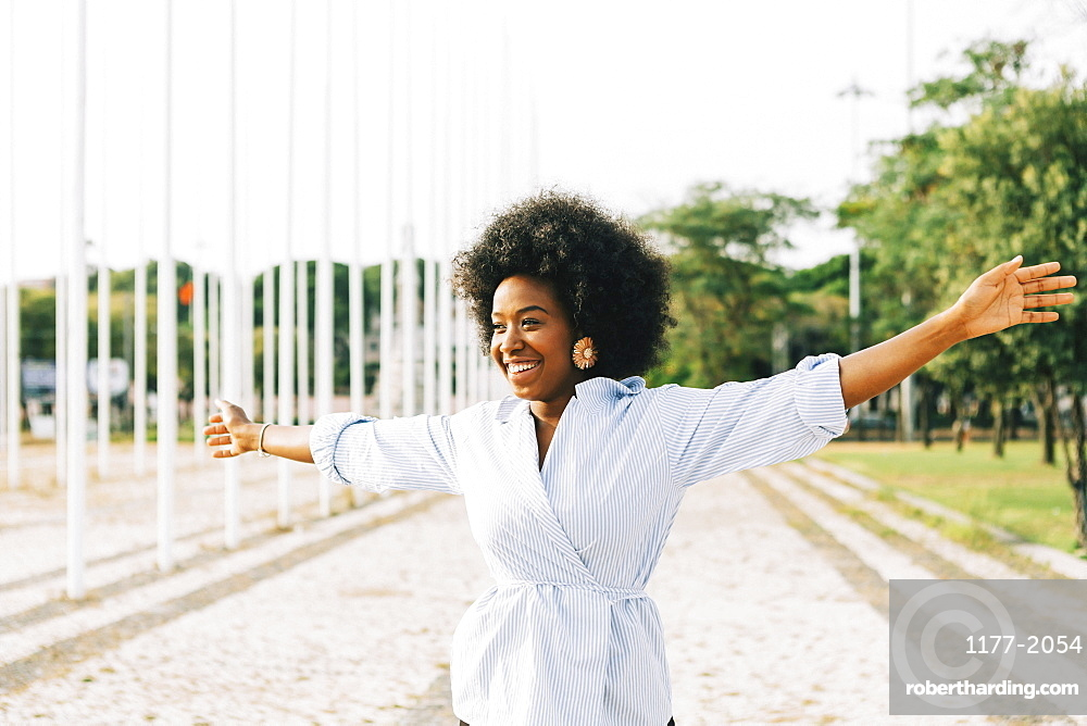 Carefree young woman with arms outstretched in sunny park