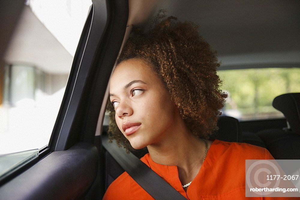 Thoughtful young woman riding in car, looking out window