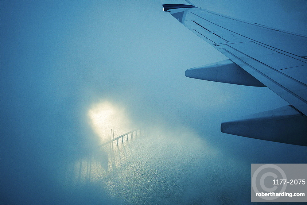 Airplane wing flying through clouds over water