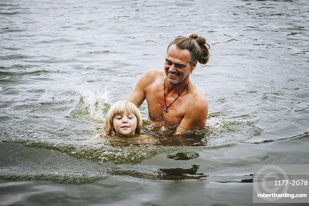 Father and son swimming in lake