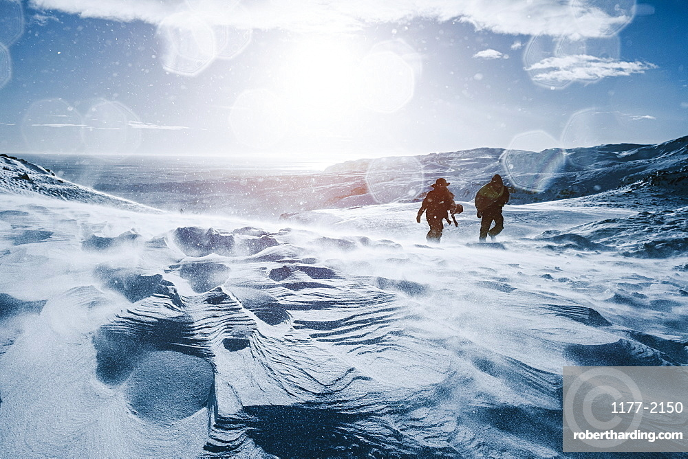 Father and son walking along sunny, snow covered mountain, Reykjadalur, Iceland