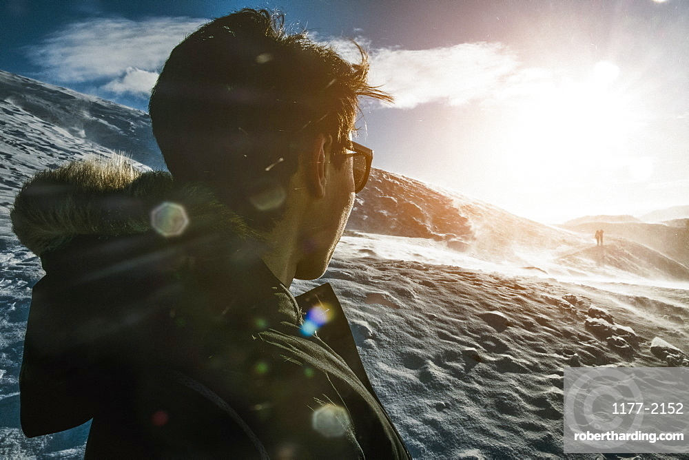 Teenage boy standing on sunny snow covered mountain, Reykjadalur, Iceland