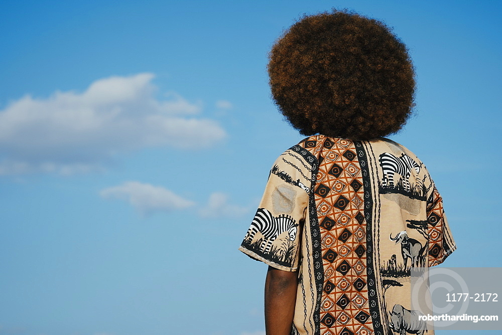 Young man with afro looking up at clouds in blue sky