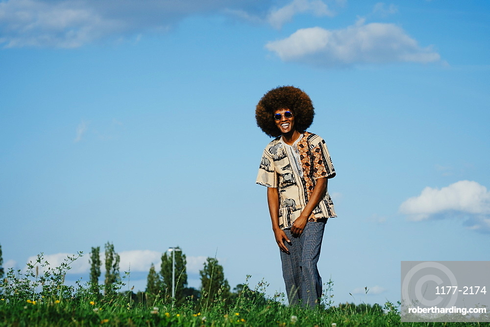 Portrait happy young man with afro in park grass