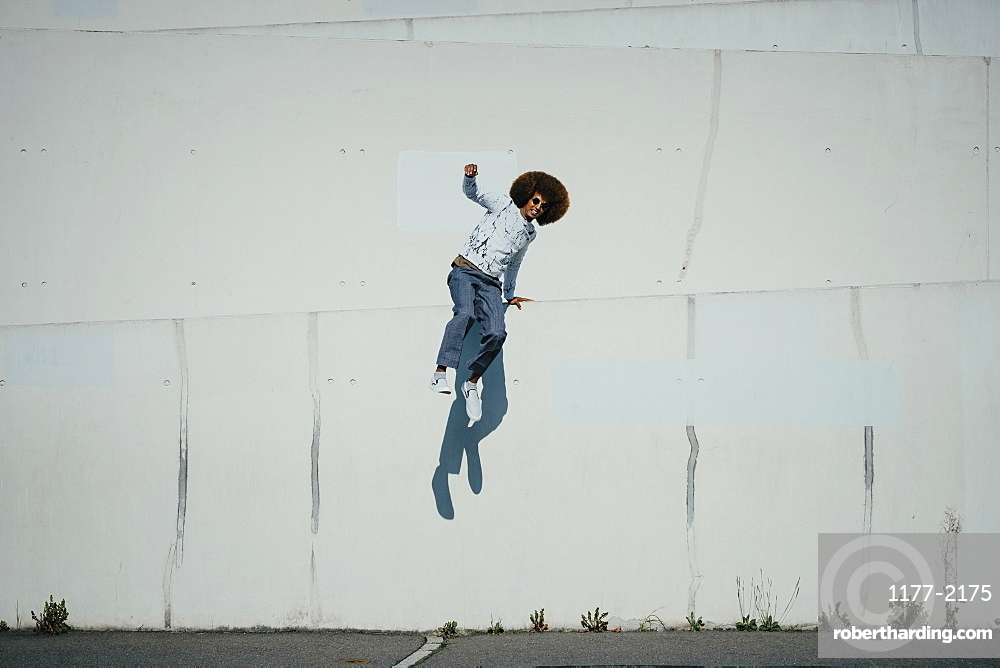 Portrait carefree young man with afro jumping at sunny wall
