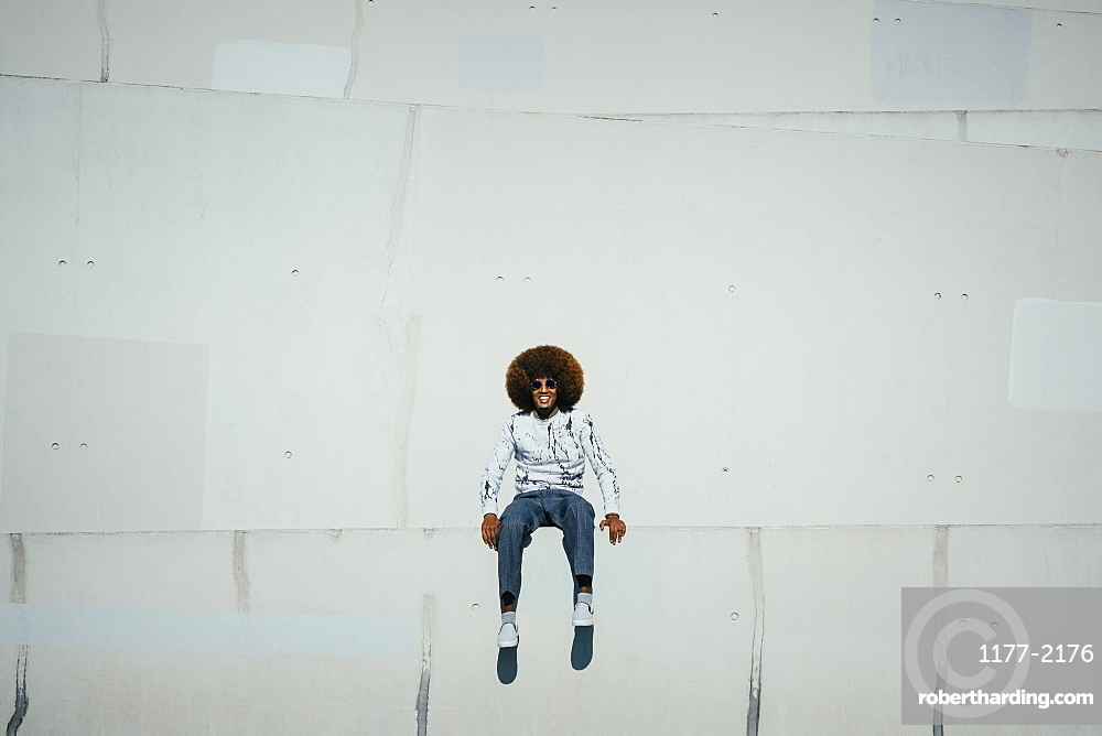 Portrait happy young man with afro sitting on wall