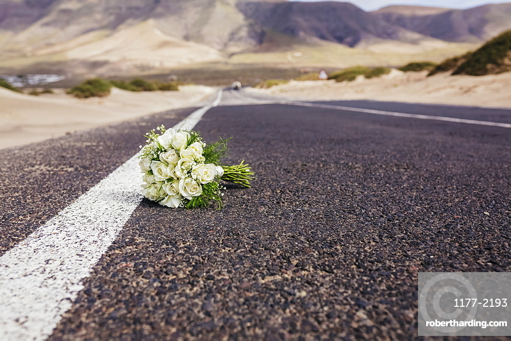 Bridal bouquet with roses laying on remote road