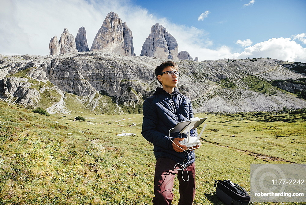 Boy with digital tablet and joystick controlling drone in sunny Drei Zinnen Nature Park, South Tyrol