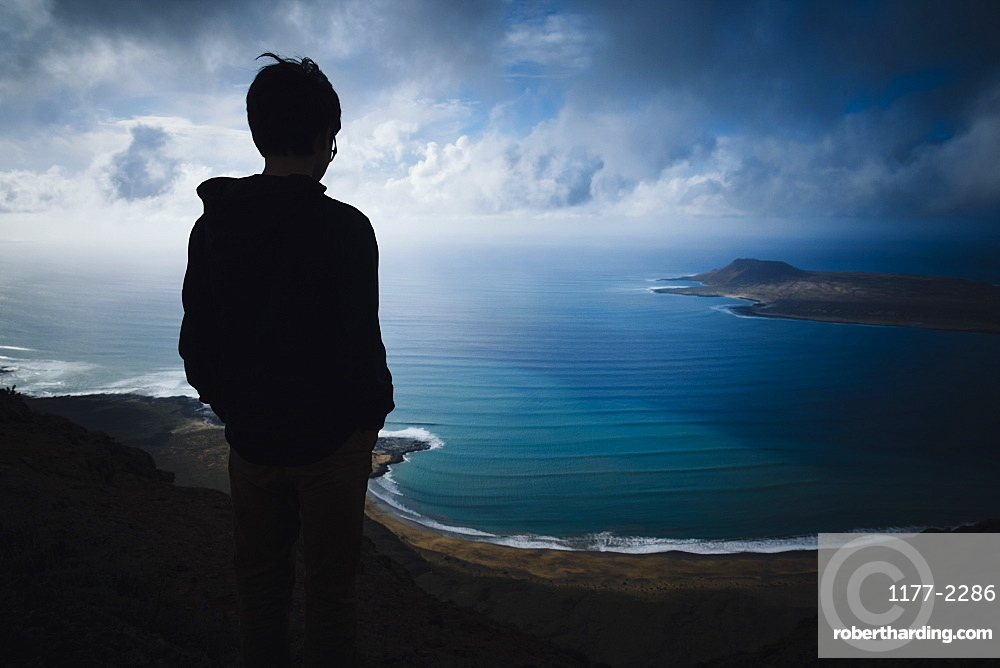 Boy looking at scenic ocean bay view with storm clouds overhead, Lanzarote, Canary Islands, Spain