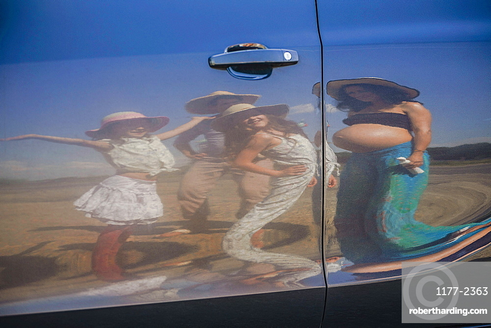 Reflection of pregnant woman and family on sunny car door