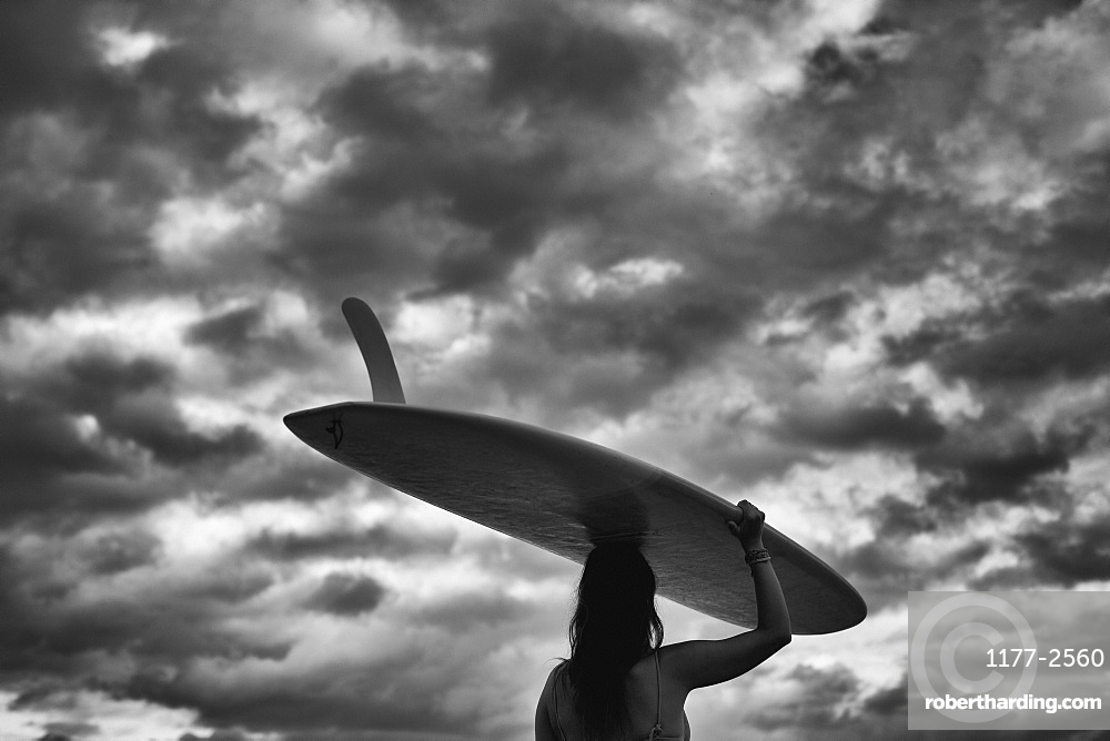 Female surfer carrying long board overhead under cloudy sky