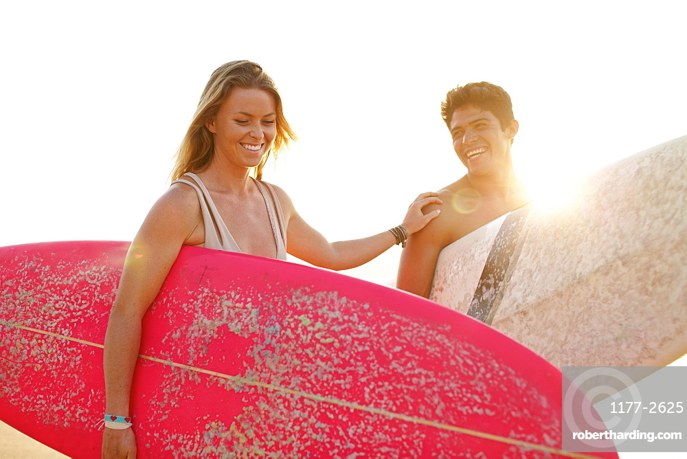 Happy young couple with surfboards