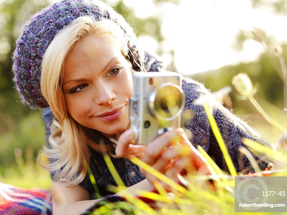 A woman photographing while lying in grass